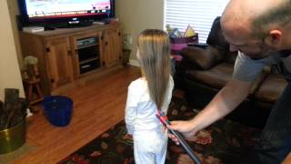 Father Puts Daughters Hair in Ponytail with Vacuum